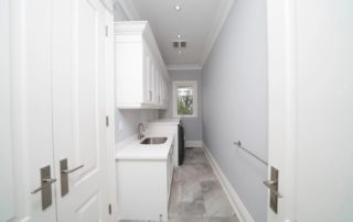 Narrow Space Laundry Room With All White Cabinetry